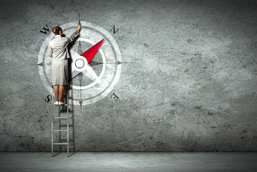 Businesswoman drawing compass with finger on wall standing on ladder.jpeg