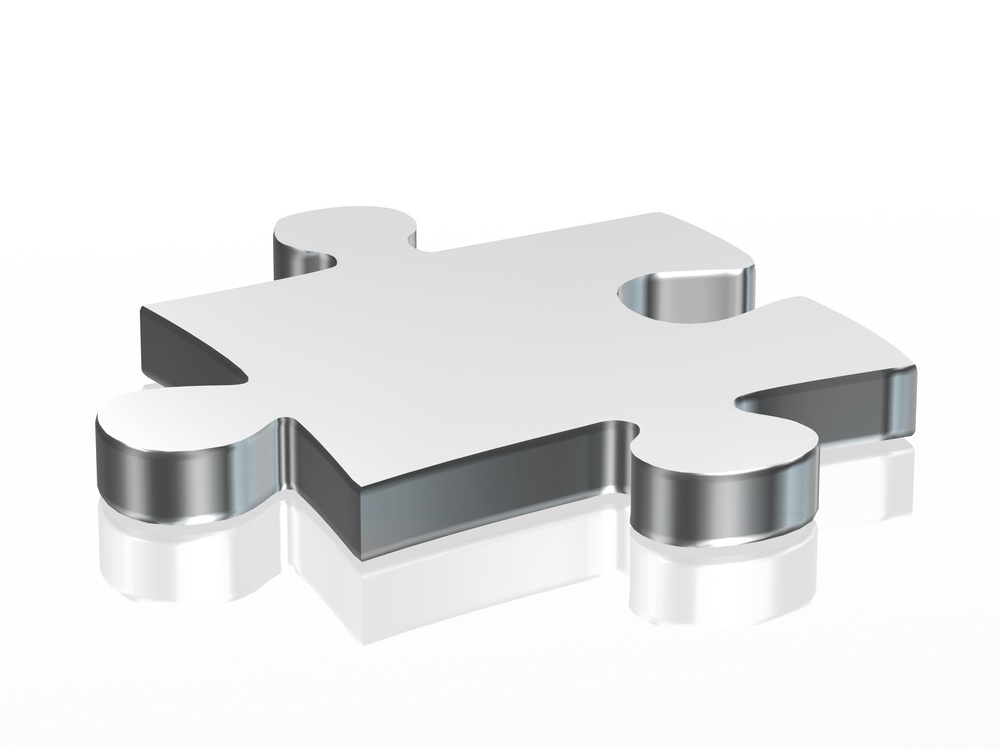 Jigsaw puzzle piece in silver over a white background
