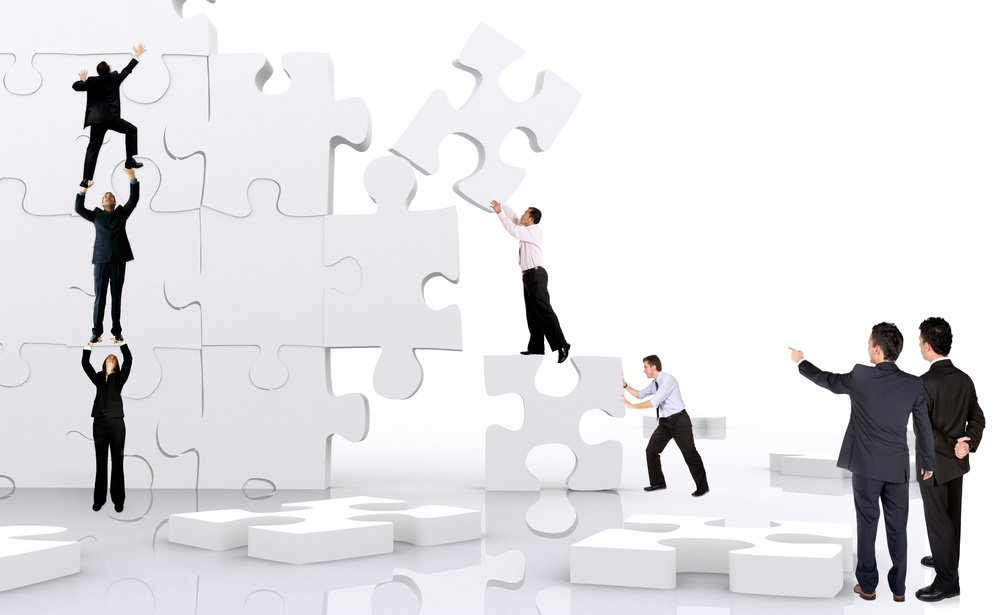 business team work building a puzzle isolated over a white background.jpeg